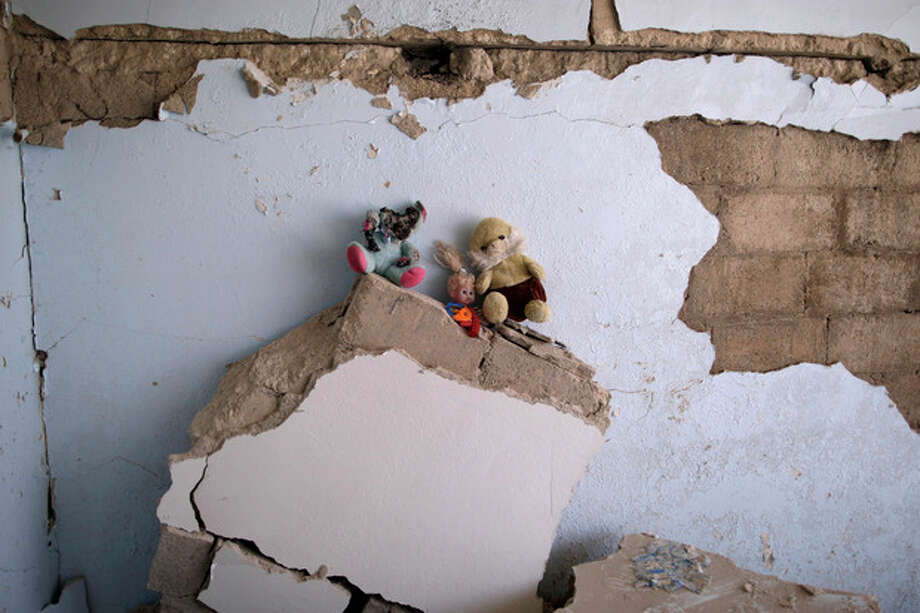 In this Wednesday, Aug. 29, 2012 photo, dolls that belonged to Sara, 11, and Youssuf Makour, 1.5, who died in a Syrian government airstrike on August, 15, 2012, that killed more than 40 people and destroyed more than a dozen of houses, were collected by their uncle Mahmoud and left on the rubble, in Azaz, on the outskirts of Aleppo, Syria. Over the past week, survivors and relatives have returned daily to collect from the rubble what can be salvaged as they also relive the day of the airstrike. (AP Photo/Muhammed Muheisen) / AP