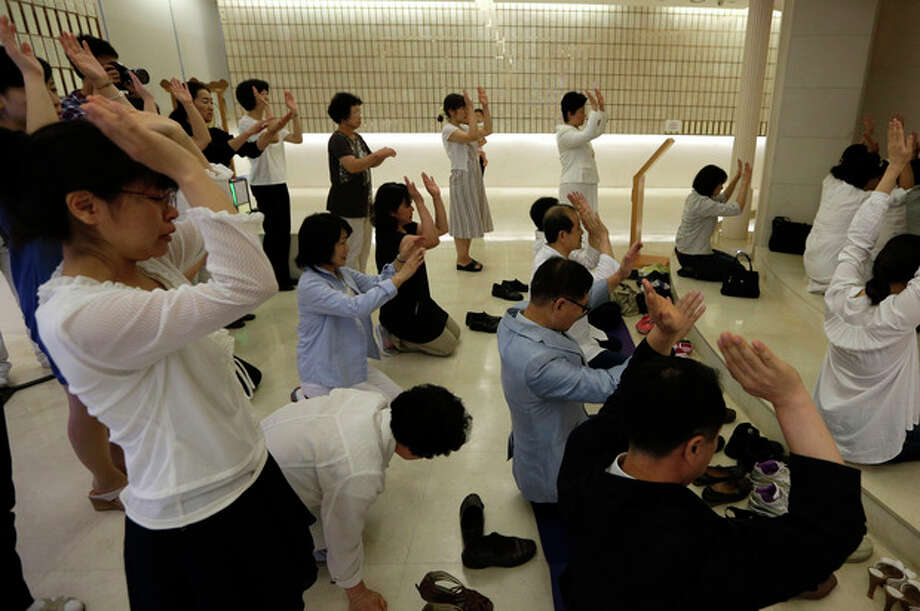 Followers pray for the Rev. Sun Myung Moon, during a service at a Unification church in Seoul, South Korea, Monday, Sept. 3, 2012. Moon, the self-proclaimed messiah who founded the church, died Monday, Sept. 3, 2012, at a church-owned hospital near his home in Gapyeong County, northeast of Seoul, church officials said. He was 92. (AP Photo/Lee Jin-man) / AP