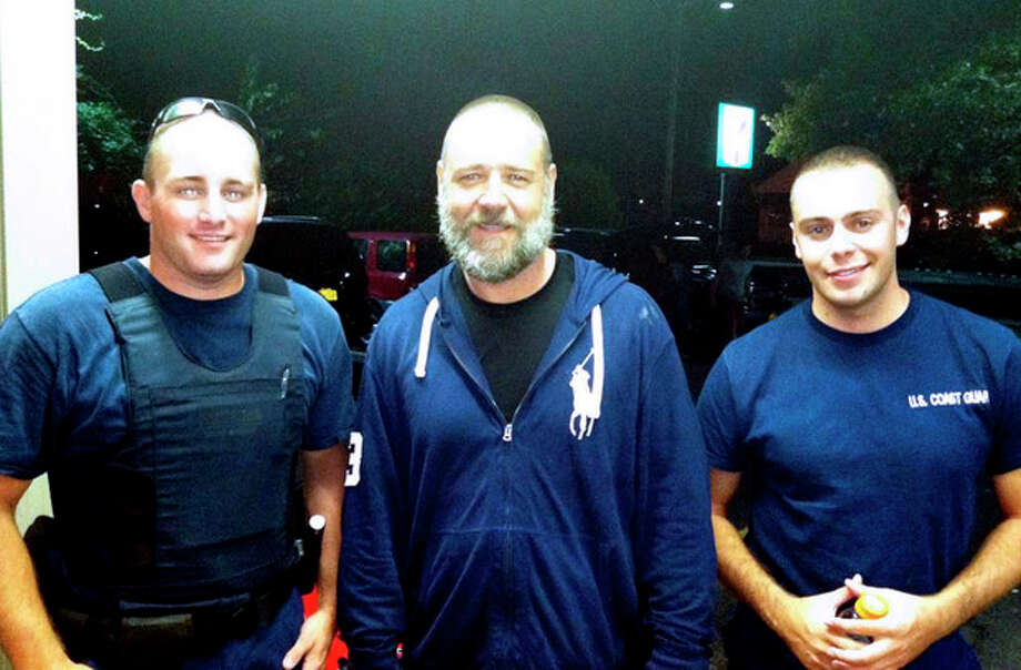 A photo provided by the U.S. Coast Guard shows Russell Crowe, center, with Coast Guard petty officers Robert Swieciki, left, and Thomas Watson Sunday Sept. 2, 2012. Crowe and a friend became disoriented while kayaking in Long Island Sound Sunday and called the Coast Guard for assistance. (AP Photo/U.S. Coast Guard) / U.S. Coast Guard