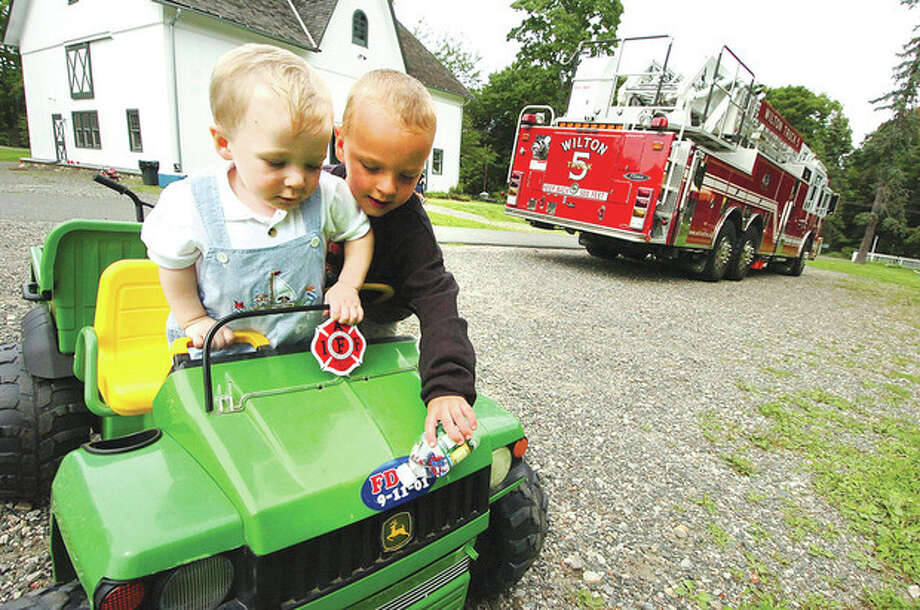 Hour Photo/ Alex von Kleydorff. l-R Grandson Dalton Dolnier and Cole Johnson play in a smaller version of a fire truck at the retirement party for Karl Dolnier on Sunday. / 2012 The Hour Newspapers