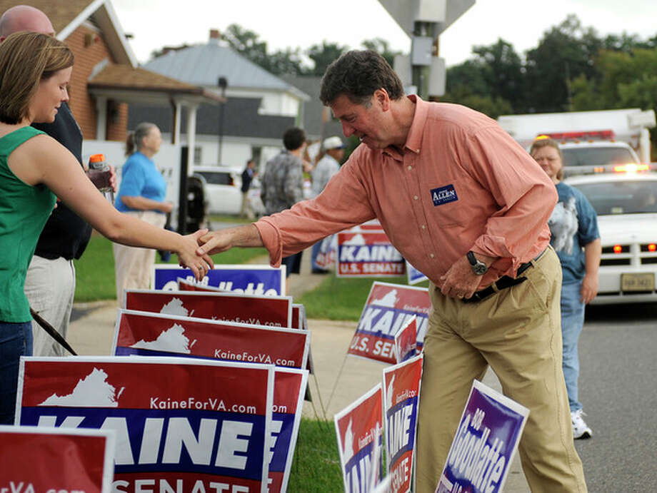 Republican senatorial candidate George Allen shakes the hand of a woman over a line of political signs supporting Democrat opponent Tim Kaine. Green space near roads and public areas were choked with political advertising during the Labor Day parade in Buena Vista, Va. The parade is the first big political event of the season in the Shenandoah Valley. (AP Photo/The Daily News Leader, Pat Jarrett) / The News Leader