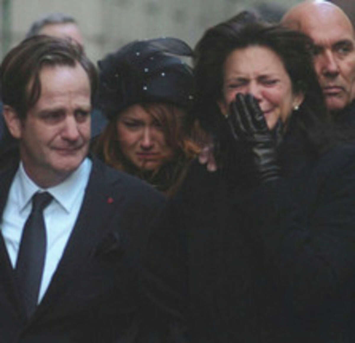 Matthew Badger, left, and Madonna Badger, the parents of three children that were killed in a fire on Christmas Day, react as the children's coffins are carried into a church during their funeral in Manhattean Jan. 5. Hour photo / Erik Trautmann