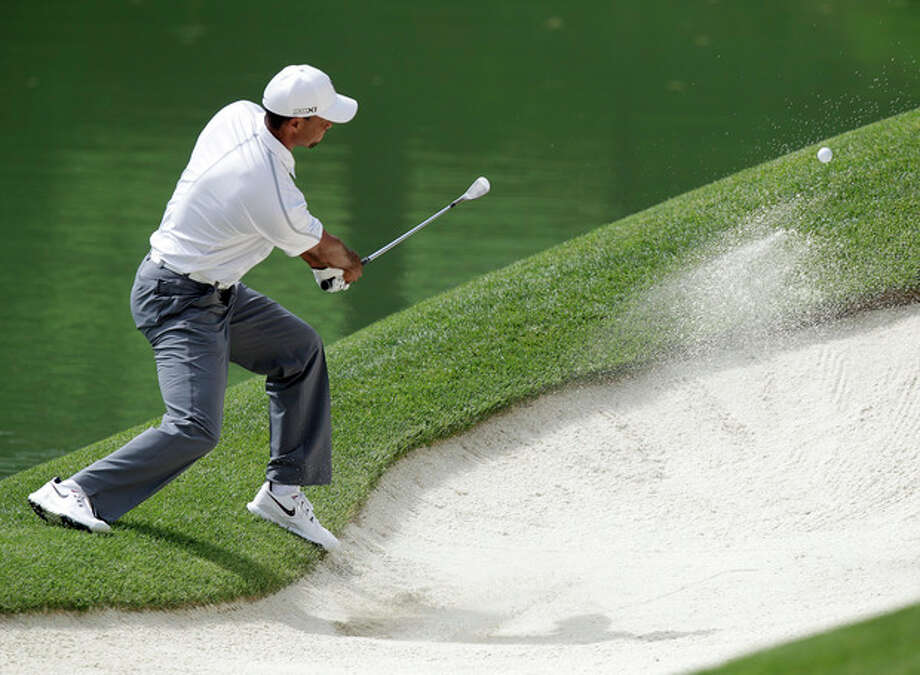 Tiger Woods hits from the bunker on the 12th hole during the third round of the Memorial golf tournament Saturday, June 1, 2013, in Dublin, Ohio. (AP Photo/Jay LaPrete) / FR52593 AP