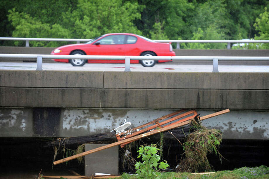 Flood debris is seen wedged underneath a bridge as a motorist passes on Park Avenue in Paducah, Ky., June 1, 2013. Severe weather overnight brought 6 to 8 inches of rain to the region. (AP Photo/Stephen Lance Dennee) / FR170568 AP