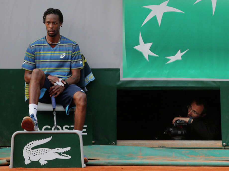 A man looks at Gael Monfils of France, left, as he rest on the seat of a lines man in his third round match against Tommy Robredo of Spain at the French Open tennis tournament, at Roland Garros stadium in Paris, Friday, May 31, 2013. Robredo won in five sets 2-6, 6-7, 6-2, 7-6, 6-2. (AP Photo/Michel Spingler) / AP