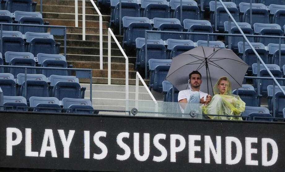 Tennis fans use an umbrella during a rain delay of a match between Victoria Azarenka, of Belarus, and Samantha Stosur, of Australia, in the quarterfinals of the 2012 US Open tennis tournament, Tuesday, Sept. 4, 2012, in New York. (AP Photo/Kathy Willens) / AP