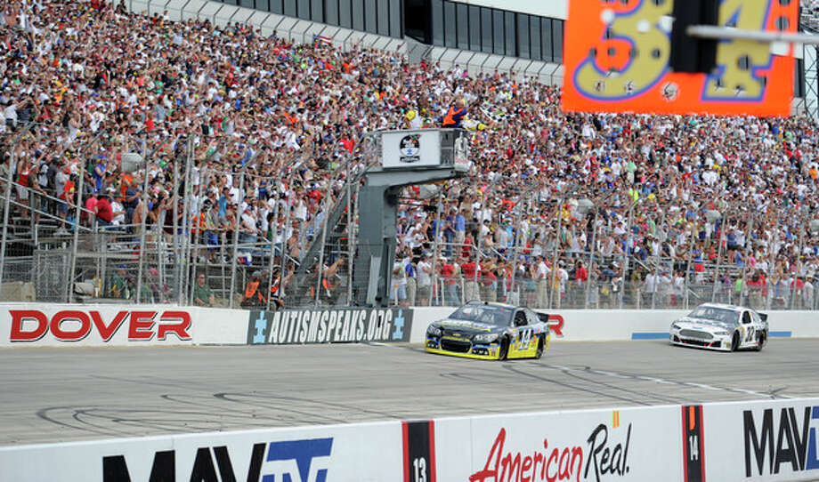 Tony Stewart (14) takes the checkered flag to win a NASCAR Sprint Cup Series auto race, Sunday, June 2, 2013, at Dover International Speedway in Dover, Del. Also seen is driver Timmy Hill (32). (AP Photo/Nick Wass) / FR67404 AP