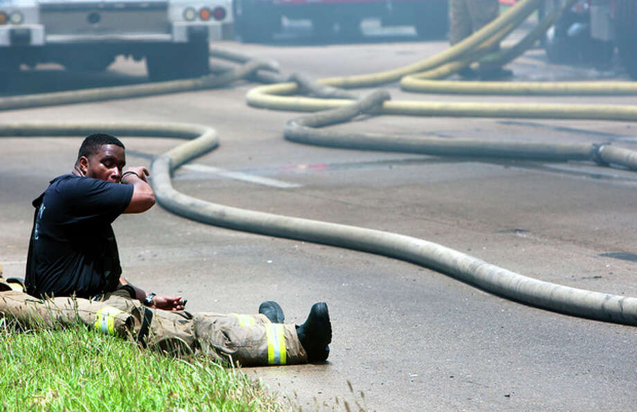 A firefighter sits on the ground during a blaze at the Southwest Inn on U.S. 59 in Houston on Friday, May 31, 2013. (AP Photo/Houston Chronicle, Cody Duty) / Houston Chronicle