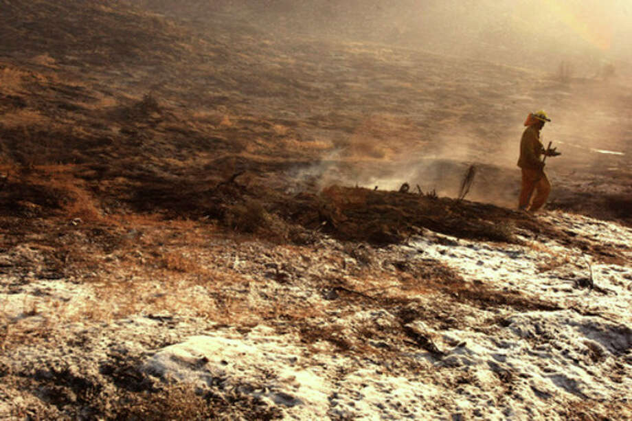 A firefighter finishes hitting a hot spot against a charred landscape caused by the Powerhouse fire along Elizabeth Lake Road in Green Valley on Sunday, June 2, 2013. The fire has burned close to 20,000 acres of land and some structures were damaged by the blaze. (AP Photo/Los Angeles Times, Genaro Molina) NO FORNS; NO SALES; MAGS OUT; ORANGE COUNTY REGISTER OUT; LOS ANGELES DAILY NEWS OUT; VENTURA COUNTY STAR OUT; INLAND VALLEY DAILY BULLETIN OUT; MANDATORY CREDIT, TV OUT / Los Angeles Times