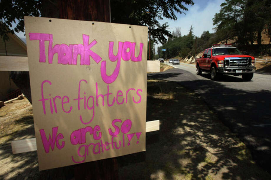 A sign shows gratitude to the firefighters who saved homes from the Powerstation fire in Lake Hughes on Sunday, June 2, 2013. Erratic winds fanned a blaze in the Angeles National Forest to nearly 41 square miles early Sunday, after fast-moving flames triggered the evacuation of nearly 1,000 homes in Lake Hughes and Lake Elizabeth, officials said. (AP Photo/Los Angeles Times, Genaro Molina) NO FORNS; NO SALES; MAGS OUT; ORANGE COUNTY REGISTER OUT; LOS ANGELES DAILY NEWS OUT; VENTURA COUNTY STAR OUT; INLAND VALLEY DAILY BULLETIN OUT; MANDATORY CREDIT, TV OUT / Los Angeles Times