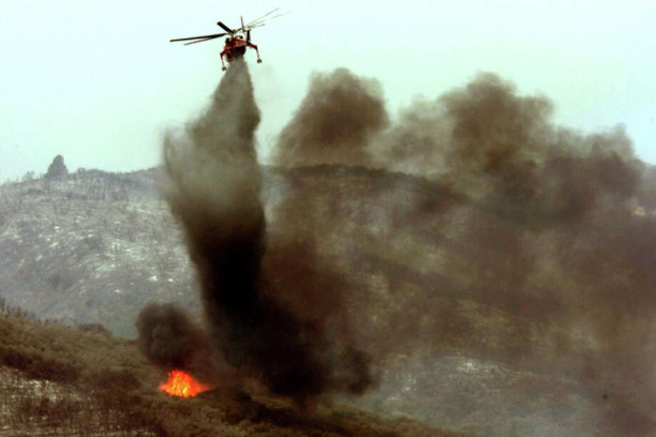 A helicopter puts out a hot spot on the Powerhouse fire at Elizabeth Lake on Sunday, June 2, 2013. Erratic winds fanned a blaze in the Angeles National Forest to nearly 41 square miles early Sunday, after fast-moving flames triggered the evacuation of nearly 1,000 homes in Lake Hughes and Lake Elizabeth, officials said. (AP Photo/Los Angeles Times, Genaro Molina) NO FORNS; NO SALES; MAGS OUT; ORANGE COUNTY REGISTER OUT; LOS ANGELES DAILY NEWS OUT; VENTURA COUNTY STAR OUT; INLAND VALLEY DAILY BULLETIN OUT; MANDATORY CREDIT, TV OUT / Los Angeles Times