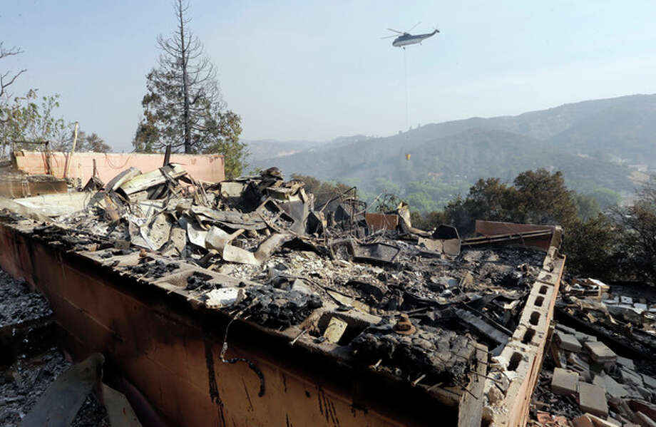 A firefighting helicopter carries a large water bucket behind a home that has been destroyed, one of at least five structures destroyed or severely damaged in what has been called the Powerhouse fire in Lake Hughes, Calif., early Sunday, June 2, 2013. Erratic wind fanned the blaze in the Angeles National Forest to nearly 41 square miles early Sunday, after fast-moving flames triggered the evacuation of nearly 1,000 homes in Lake Hughes and Lake Elizabeth, officials said. (AP Photo/Reed Saxon) / AP