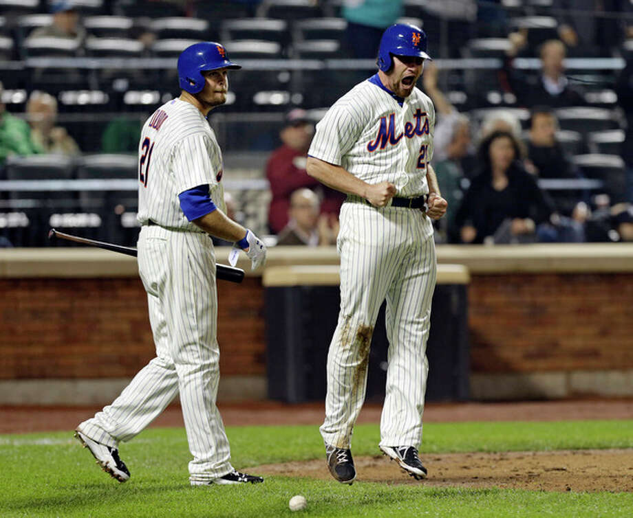 New York Mets Lucas Duda, left, watches as New York Mets Daniel Murphy (28) reacts after scoring on David Wright's double to tie the game in the ninth inning of an interleague baseball game against the New York Yankees at Citi Field in New York, Tuesday, May 28, 2013. The Mets won 2-1.(AP Photo/Kathy Willens) / AP