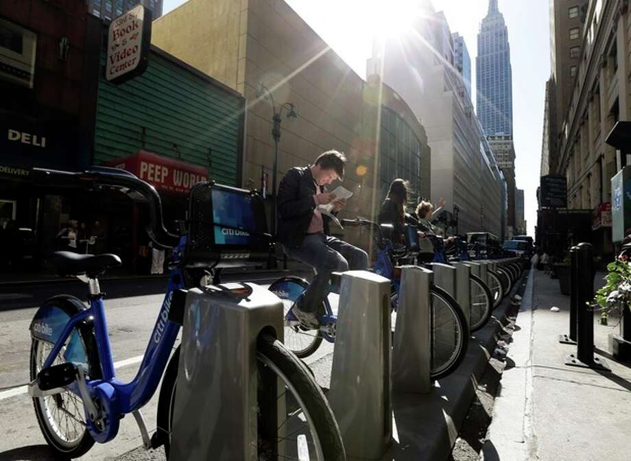 AP Photo/Frank Franklin IITourists sit on bikes that are available as part of a bike share program Monday, May 27, 2013, in New York. The privately funded Citi Bike bike-share program will launch with 6,000 bikes at 330 docking stations in Manhattan and parts of Brooklyn. Officials hope to expand to 10,000 bikes and 600 docking stations in Manhattan, Brooklyn and Queens. / AP
