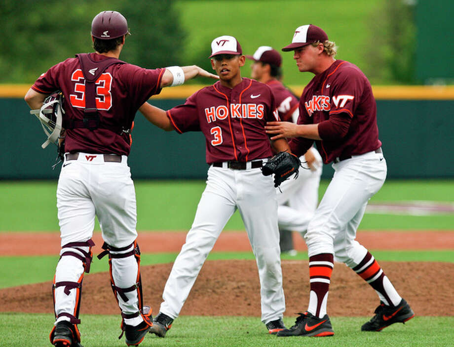 Virginia Tech's Clark Labitan, center, celebrates with teammates Chad Morgan (33) and Joe Mantiply, right, after an NCAA college baseball tournament regional game against Connecticut at English Field in Blacksburg, Va., Sunday, June 2, 2013. (AP Photo/Michael Shroyer) / FR 170944 AP