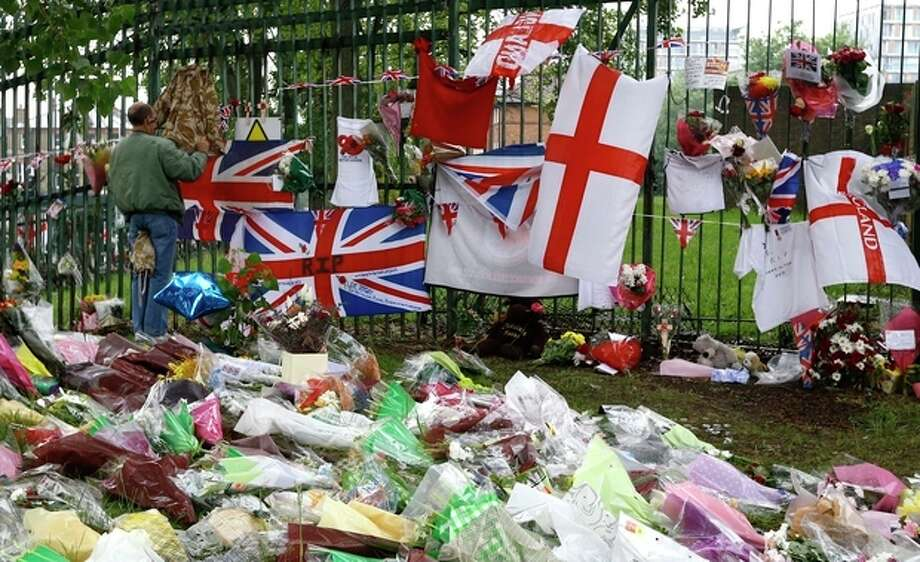 Some of the thousands of floral and other tributes left at the scene near Woolwich Barracks in London, Tuesday, May 28, 2013, where 25-year-old soldier of the Royal Regiment of Fusiliers Lee Rigby was attacked and killed last week. Two men attacked and killed the soldier in broad daylight Wednesday May 22. Thousands of floral tributes have been left by public well wishers. (AP Photo/Kirsty Wigglesworth) / AP