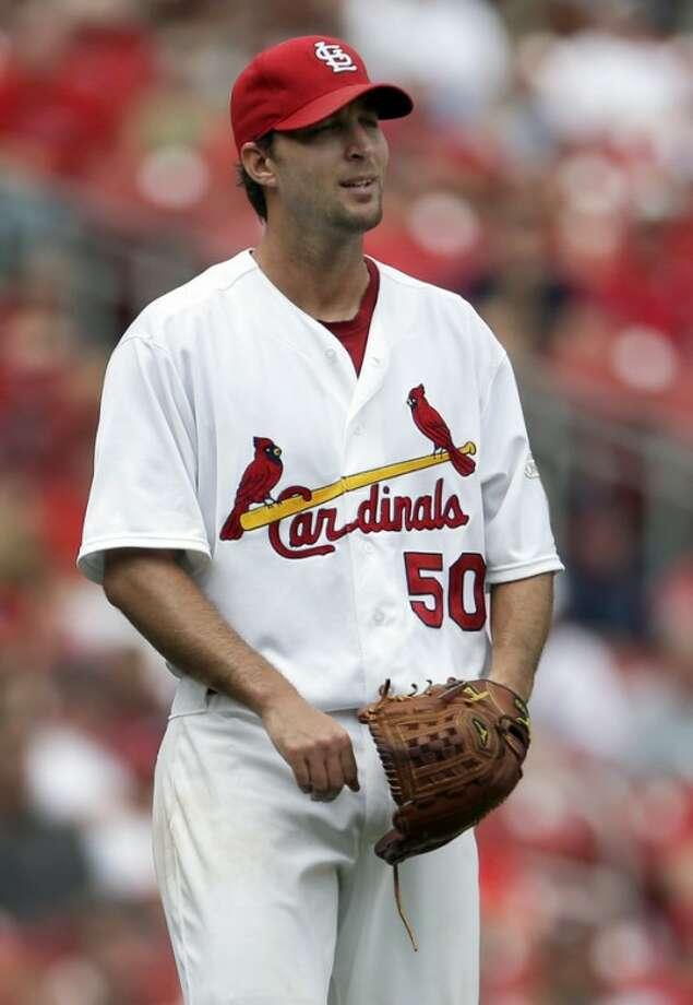 St. Louis Cardinals starting pitcher Adam Wainwright watches as a ball hit for a three-run home run by New York Mets' Ike Davis leaves the park during the fifth inning of a baseball game Wednesday, Sept. 5, 2012, in St. Louis. (AP Photo/Jeff Roberson)