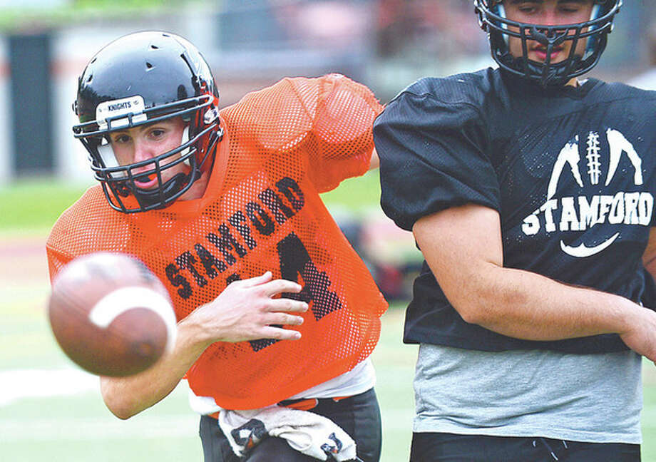 Photo by Erik TrautmannStamford High football captain Tyler Kane looks for a loose ball in practice Tuesday.