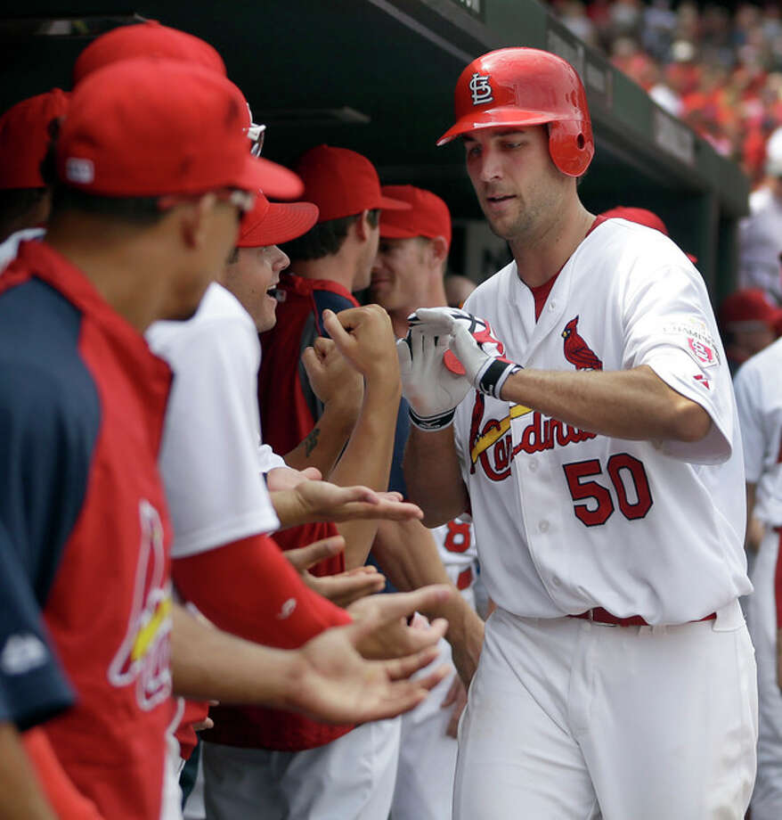 St. Louis Cardinals' Adam Wainwright is congratulated by teammates in the dugout after hitting a solo home run during the third inning of a baseball game against the New York Mets, Wednesday, Sept. 5, 2012, in St. Louis. (AP Photo/Jeff Roberson) / AP