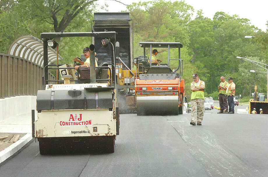 Hour Photo/Alex von Kleydorff Cres work at paving the Triangle Street Bridge on Tuesday. / 2013 The Hour Newspapers