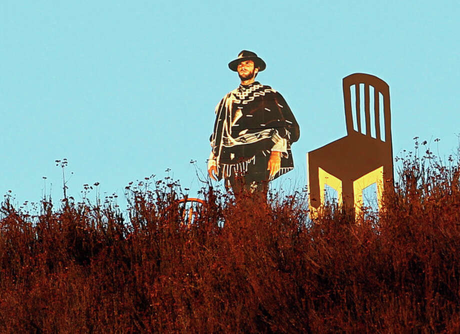 A life-sized cardboard cutout of actor Clint Eastwood next to an empty chair is seen overlooking a freeway in Glendale, Calif., Tuesday, Sept. 4, 2012. The chair is a reference to Eastwood's 12-minute speech during last week's Republican National Convention that drew both criticism and praise for Eastwood. Life-sized cardboard cutouts of Eastwood, John Wayne and Gene Autry have been keeping watch over Glendale for months as part of an effort by Los Angeles resident Justin Stadel to spur a conversation about public art. (AP Photo/Reed Saxon) / AP