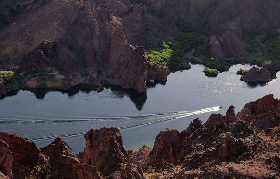 FILE - In this Friday, April 12, 2013 file photo, a patrol boat makes its way upstream along the Colorado River in Black Canyon just south of Hoover Dam near Willow Beach, Ariz. Decision-makers from seven Western states, Indian tribes and several conservation groups will be meeting in San Diego on May 28 to consider their next steps in a collaborative effort to squeeze every useable drop from the overtaxed Colorado River. The meeting comes five months after the Secretary of the Interior declared the river won't be able to meet demands over the next 50 years of a regional population now about 40 million and growing. (AP Photo/Julie Jacobson, File) / AP
