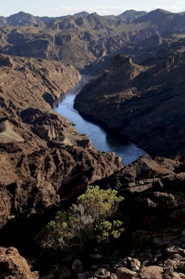 FILE - In this Friday, April 12, 2013 file photo, the Colorado River flows through Black Canyon just south of Hoover Dam near Willow Beach, Ariz. Decision-makers from seven Western states, Indian tribes and several conservation groups will be meeting in San Diego May 28 to consider their next steps in a collaborative effort to squeeze every useable drop from the overtaxed Colorado River. The meeting comes five months after the Secretary of the Interior declared the river won't be able to meet demands over the next 50 years of a regional population now about 40 million and growing. (AP Photo/Julie Jacobson, File)