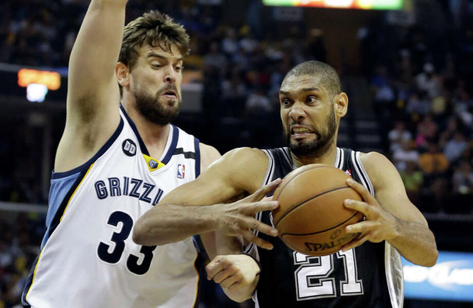 San Antonio Spurs forward Tim Duncan (21) drives to the basket as Memphis Grizzlies center Marc Gasol (33) defends, during Game 4 of the Western Conference finals NBA basketball playoff series in Memphis, Tenn., Monday, May 27, 2013. The Spurs defeated the Grizzlies 93-86 to advance to the NBA finals. (AP Photo/Danny Johnston) / AP