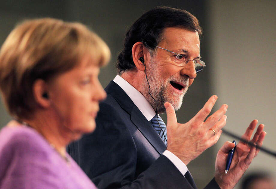 Germany's Chancellor Angela Merkel, left, and Spain's Prime Minister Mariano Rajoy, right, gesture during a press conference at the Moncloa Palace, in Madrid, Spain, Thursday, Sept. 6, 2012. (AP Photo/Andres Kudacki) / AP