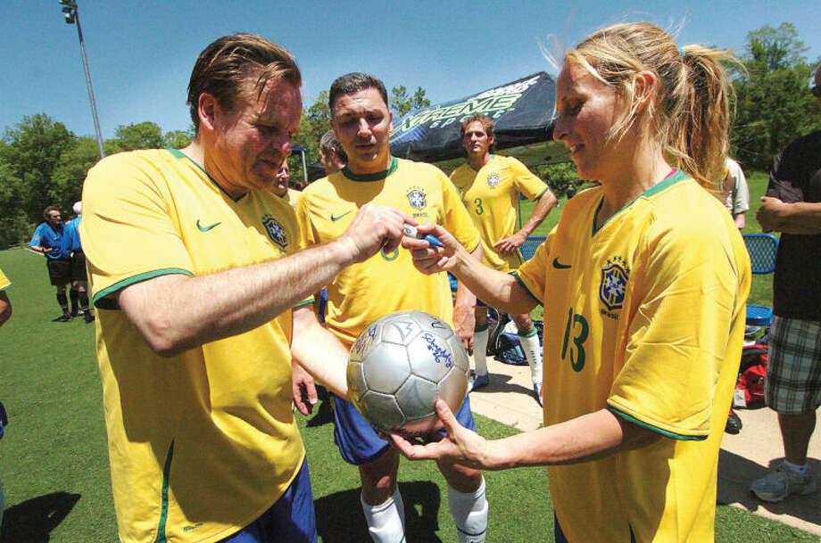 Hour Photo/Alex von Kleydorff . The Ancient Warriors team and Kristine sign a game ball.