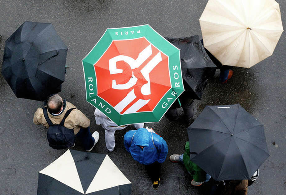 People stroll with umbrellas in the alleys of the Roland Garros stadium as rain delays the start of matches, Tuesday, May 28, 2013 in Paris. (AP Photo/Petr David Josek) / AP