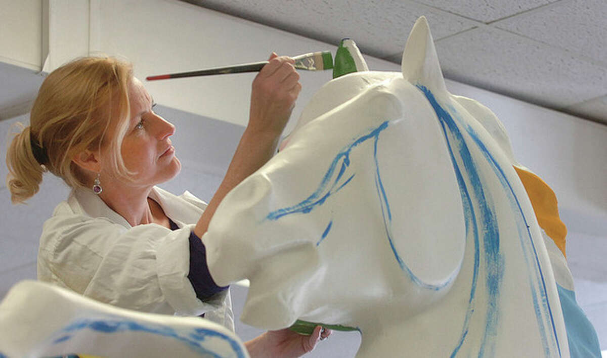 """File photo by Alex von Kleydorff. Artist Susan Waldinger paints the ear of her horse sculpture, titled 'Foal of Flora,' for the outdoor summer exhibit """"Horsin' Around Stamford Downtown."""""""