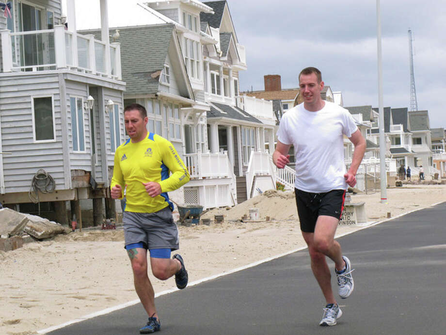 Joggers run past a house damaged by Superstorm Sandy on the Manasquan, N.J., beachfront, Saturday, May 25, 2013. Communities that were hard-hit by Superstorm Sandy, including Manasquan, are hoping for a profitable summer season to help them recover. (AP Photo/Wayne Parry) / AP