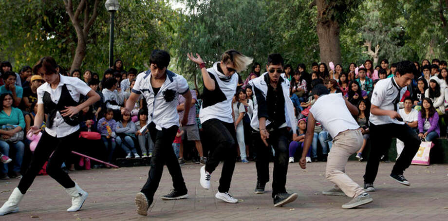 In this May 11, 2013 photo, followers of Korean pop band Big Bang, imitate the band at the Ramon Castilla Park in Lima, Peru. While there's little hard data, there's no questioning the fervor of the fans who turn up at Ramon Castilla Park each Saturday and emulate the dances of K-pop bands. (AP Photo/Martin Mejia) / AP