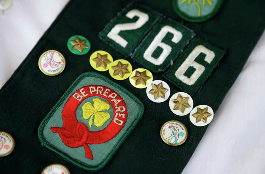 This Tuesday, May 14, 2013 photo shows pins on the childhood Girl Scouts sash of Joni Kinsey, in Iowa City, Iowa. In an effort to save money, Girl Scout councils across the country are making proposals that would have been unthinkable a generation ago: selling summer camps that date back to the 1950s. (AP Photo/Charlie Neibergall) / AP