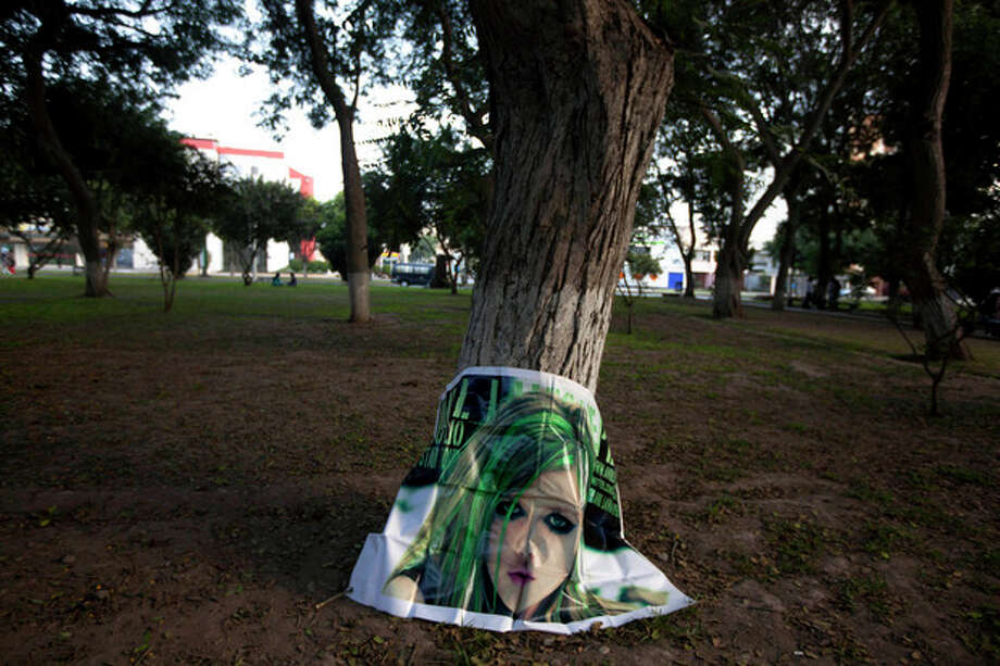 In this May 11, 2013 photo, a poster of South Korean K-pop singer Woorissica stands against a tree trunk after it was left behind by fans who gathered here in Ramon Castilla park in Lima, Peru. Teenagers throughout Latin America have long looked north for pop music inspiration. Now the East is rising, with a large and enthusiastic cult of fans in some countries following the K-pop music from Korea. (AP Photo/Martin Mejia) / AP