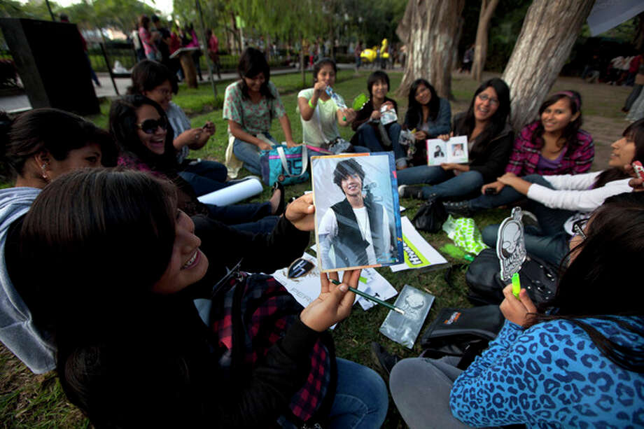 In this May 11, 2013 photo, a fan of South Korean singer Hyun Joong shows her picture of him as she sits with other fans as they celebrate the singer's birthday in Ramon Castilla park in Lima, Peru. Hundreds of fans of K-pop gather each week in the downtown park to dance to the energetic music. Some dress up as Korean comic book characters. (AP Photo/Martin Mejia) / AP