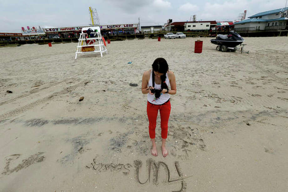 In this Friday, May 24, 2013 photo, Jasmine Wilker, 15, of Robbinsville, N.J., takes a photograph of writing she put on the sand on the beach, in Seaside Heights, N.J. The Jersey Shore beaches officially opened for the summer on Friday, after rebuilding following the destruction left behind by Superstorm Sandy last fall. The storm caused $37 billion of damage in the state. (AP Photo/Julio Cortez) / AP