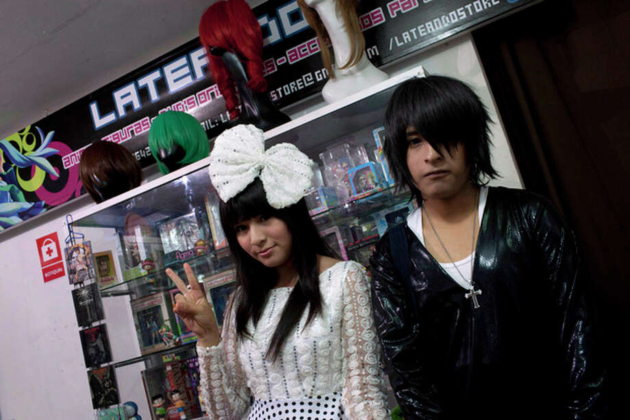 In this May 4, 2013 photo, Sandra and Gabriel, who did not give their last names, pose for a photo in their costumes in the style of characters from South Korean comic books at the Arenales shopping center in Lima, Peru. The Arenales shopping center has entire floors dedicated to South Korean music, clothes and food. (AP Photo/Martin Mejia) / AP