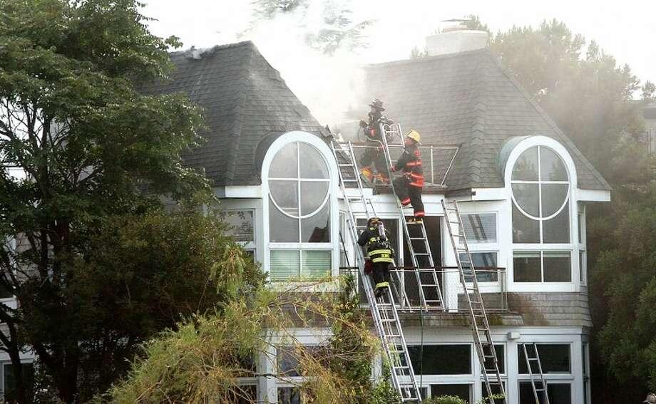 Hour Photo/ Alex von Kleydorff. Westport Firefighters battle a fire on Harbor Rd Thursday afternoon