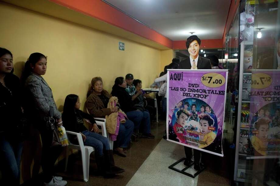 In this May 4, 2013 photo, parents and their children wait for a store to open that sells Korean pop music, known as K-Pop, at the Arenales shopping center in Lima, Peru. Arenales has entire floors dedicated to South Korean music, clothes and food. (AP Photo/Martin Mejia) / AP