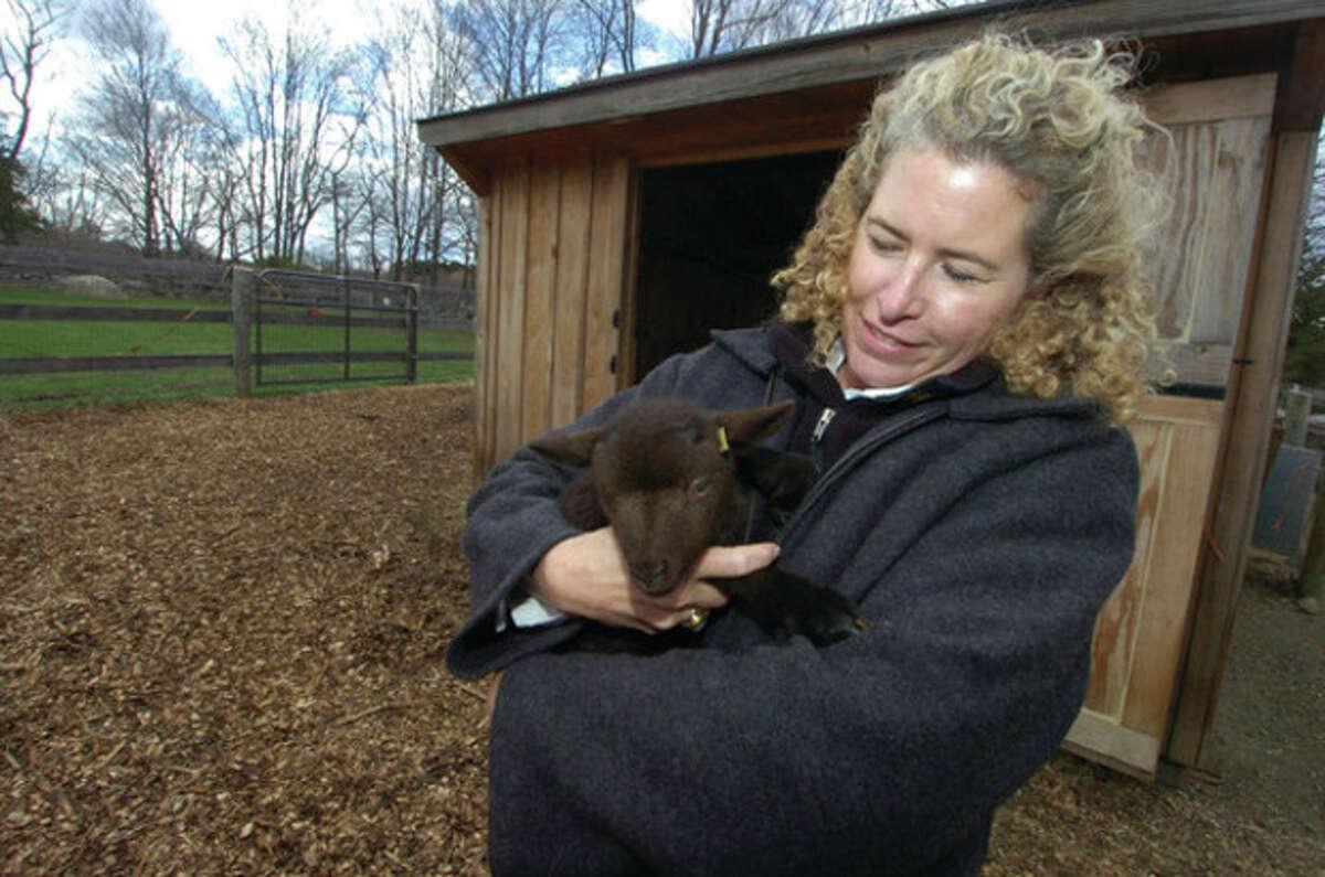 File photo by Alex von Kleydorff Millstone Farm owner Betsy Fink holds on to a newborn lamb at the 180 Millstone Road farm.