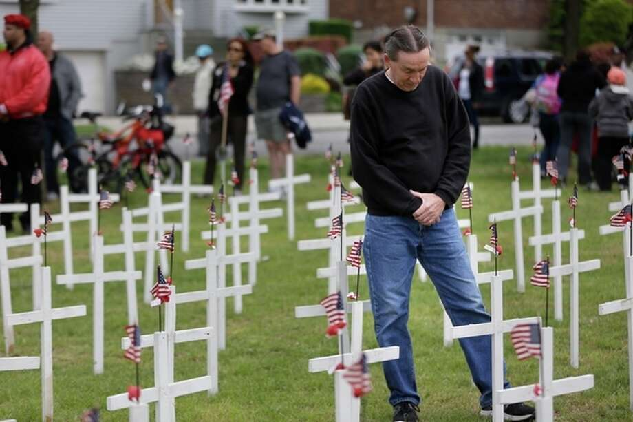 AP Photo/Seth WenigJoe Schulmann pauses in prayer over a cross bearing the name of his neighbor, Michael Wick, who was killed during the Vietnam War, at the College Point Memorial Day Parade in New York, Sunday, May 26. / AP