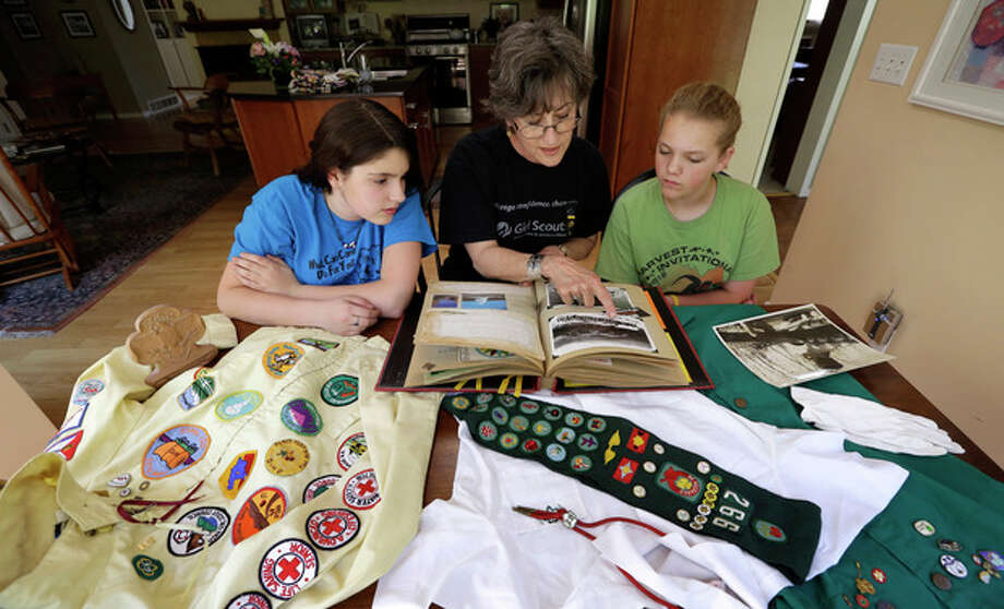In this Tuesday, May 14, 2013 photo, Joni Kinsey, of Iowa City, Iowa, shows some of her Girl Scouts memorabilia to two girls in her troop in Iowa City, Iowa. In an effort to save money, Girl Scout councils across the country are making proposals that would have been unthinkable a generation ago: selling summer camps that date back to the 1950s. (AP Photo/Charlie Neibergall) / AP