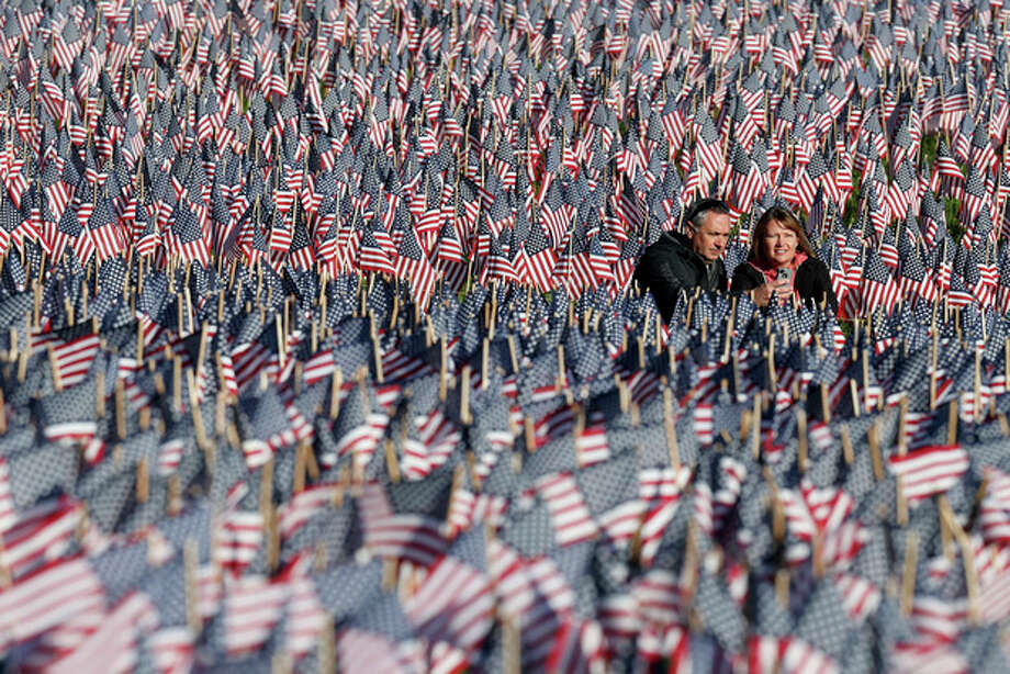 A couple photograph themselves amongst a sea of flags on Boston Common in Boston, Sunday, May 26, 2013. The flags were placed by the Massachusetts Military Heroes Fund in memory of every fallen Massachusetts service member from the Civil War to the present. (AP Photo/Michael Dwyer) / AP