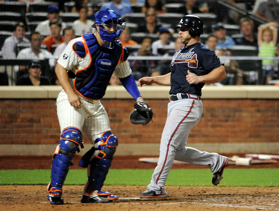 Atlanta Braves' Dan Uggla scores at home plate on a sacrifice fly by David Ross as New York Mets catcher Kelly Shoppach waits for the throw in the seventh inning of a baseball game on Friday, Sept. 7, 2012, at Citi Field in New York. (AP Photo/Kathy Kmonicek) / FR170189 AP