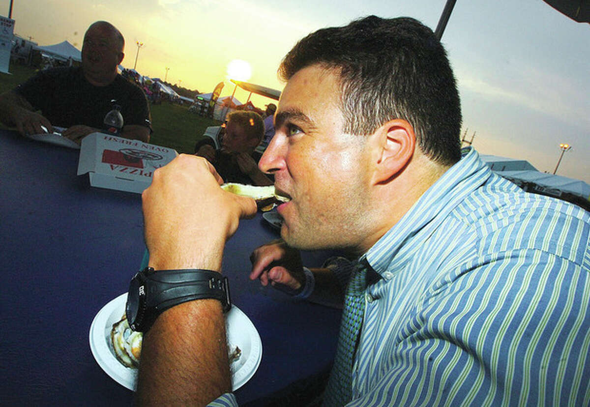 Hour Photo/ Alex von Kleydorff. Joe Alessandro from Brookfield digs into a dozen fresh oyster from Flotilla 72 at the 2012 Oyster Festival