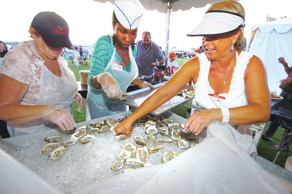 Hour Photo/ Alex von Kleydorff. l-r Mary Tillinghast, Sabine Lezeau and Sandy Schmitt set out more fresh shucked oysters for the crowds at Flotilla 72 at the 2012 Oyster Festival