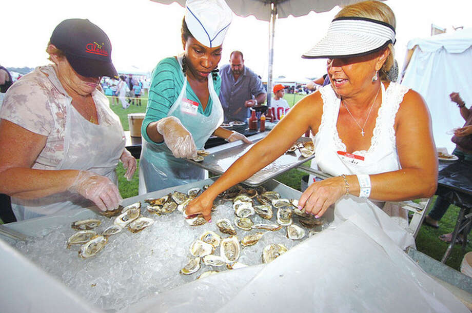 Hour Photo/ Alex von Kleydorff. l-r Mary Tillinghast, Sabine Lezeau and Sandy Schmitt set out more fresh shucked oysters for the crowds at Flotilla 72 at the 2012 Oyster Festival / 2012 The Hour Newspapers