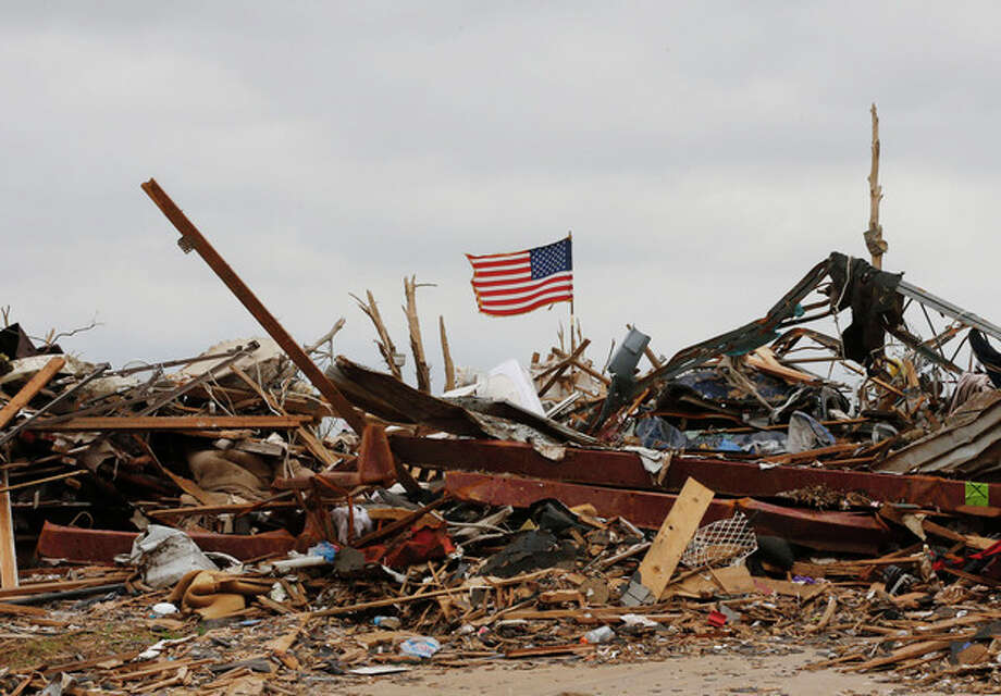 A flag continues to fly amidst the remains of tornado destroyed homes in Moore, Okla., Monday, May 27, 2013. (AP Photo/Sue Ogrocki) / AP